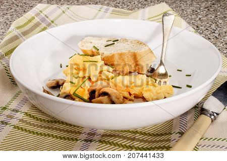 scrambled eggs with mushrooms and chives served in a deep plate
