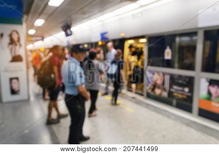 blurred image of people queuing and waiting for subway with security guard at train station, transport in rush hour, people lifestyle, transportation concept