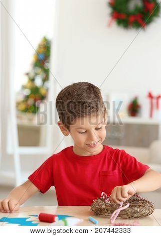 Cute boy decorating Christmas wreath on table