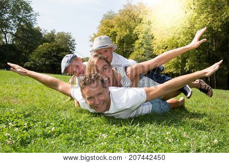 Cheerful Family In A Park, Dad, Mum And Heir Two Lovely Son Are Lying On The Grass While They Are Lo