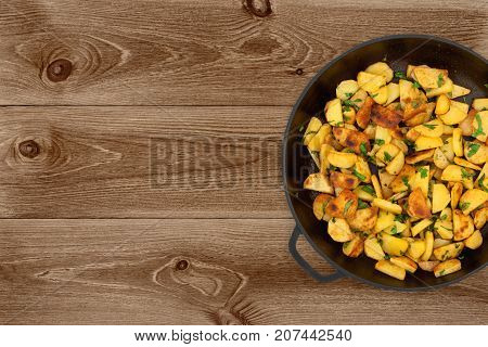 Fried potatoes in a cast iron pan on dark wooden background top view