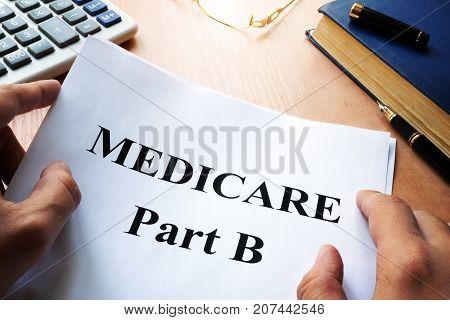 Medicare Part B on a desk. Medical insurance concept.