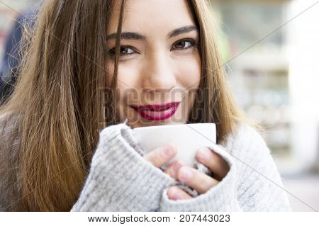 Attractive young woman is having a coffee on a street with street life background in autumn time. Lifestyle concept.