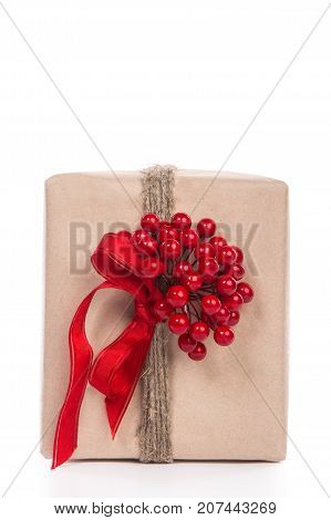 Christmas Gift Wrapped In Craft And Decorateed With Twine With A Boquette Of Little Red Berries Isol