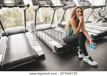 Beautiful athletic girl sits on a treadmill with a bottle of energy sports drink and smiles at the camera. Sports lifestyle.