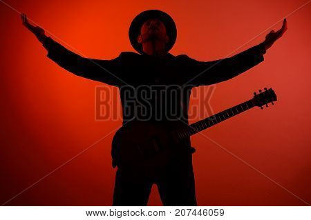 guitarist in a hat is standing with his arms outstretched on a red background