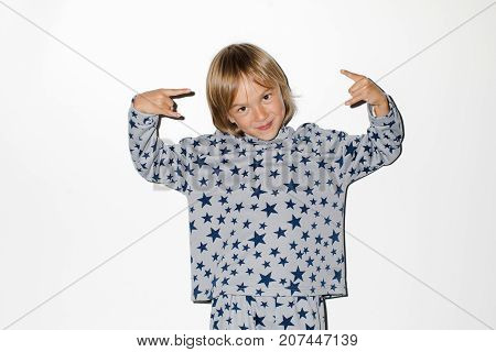 Adorable boy showing devil's horns gesture and looking at camera costume in a star