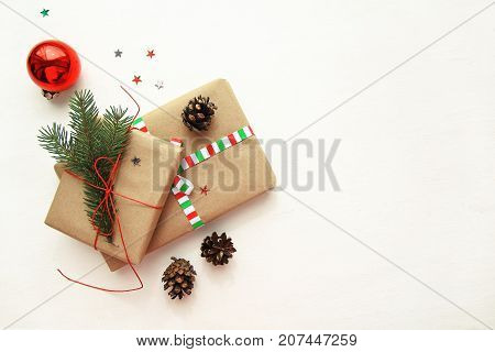 Christmas or New Year background with copy space. Handmade Christmas composition made of Xmas decorations: gifts red ball fir branch pine cones and glitter stars on textured white background. Flat lay top view.