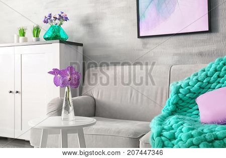 Lilac accent in modern interior. Table with flowers and comfortable couch in living room