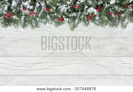 Christmas border out of natural Christmas tree fir twigs and red berries on a gray wooden background covered in snow with copy space.