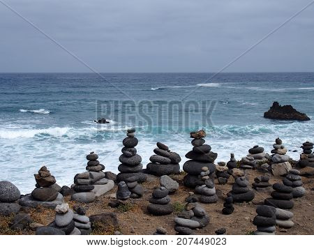 piles of stacked stones on a beach with surf waves and blue sky