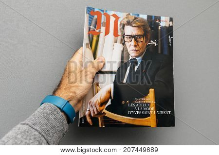 PARIS FRANCE - OCT 4 2017: Man holding M Magazine le monde with Yves Saint laurent fashion icon on the cover