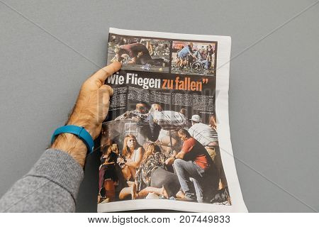 PARIS FRANCE - OCT 3 2017: Man holding Die Bild newspaper pages with socking title Pure Evil and photo after Las Vegas Strip shooting in United States