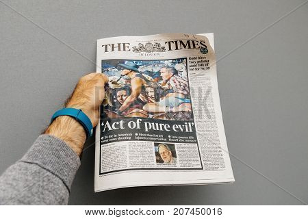 PARIS FRANCE - OCT 3 2017: Man holding The Times newspaper cover with socking title Pure Evil and photo after Las Vegas Strip shooting in United States