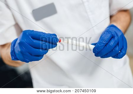 Close up view of DNA swab of saliva in doctor's hands. Men's hands in blue gloves hold DNA swab of saliva.