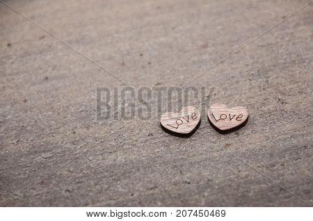 two little woden hearts showing love on dark background