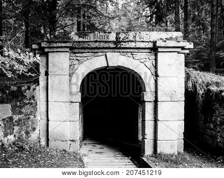 Lower entrance to tunnel of historical Schwarzenberg shipping canal, Sumava Mountains, Czech Republic. Black and white image.