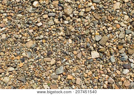 Fine gravel of warm color texture of road stone of fine fraction.