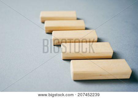 a small row of small symmetrically arranged wooden blocks