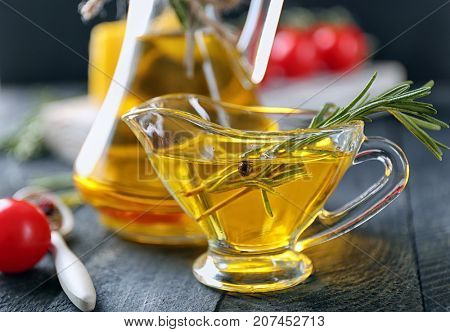 Gravy boat with rosemary oil on wooden table
