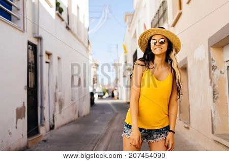 Style woman in hat and sun glasses,streets of europe.Summer vacations