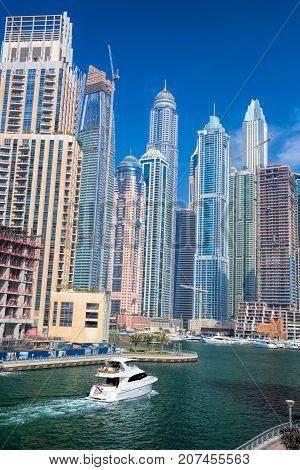 Dubai Marina with boats against skyscrapers in Dubai United Arab Emirates