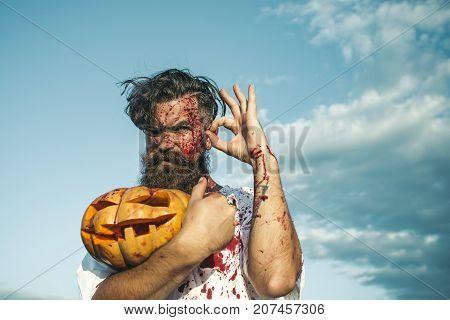 Halloween Man Holding Bloody Pumpkin On Cloudy Blue Sky