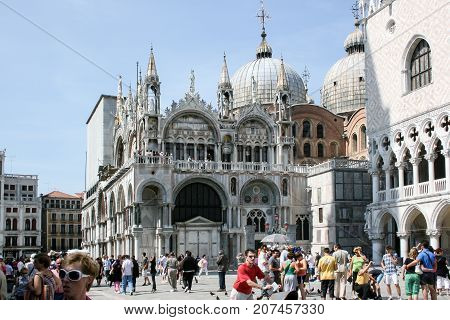 Venice, Italy - June 21, 2010: Polychrome marble facade of the Basilica di San Marco in Piazza San Marco and people walking by it