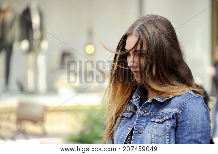 Trendy young hipster woman is looking down sadly with a blowzy hair. City style conception.