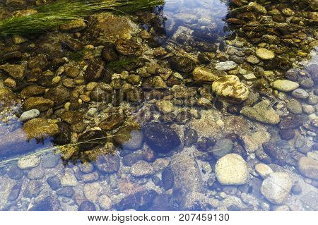 round stones at the bottom of the river under a crystal clear water