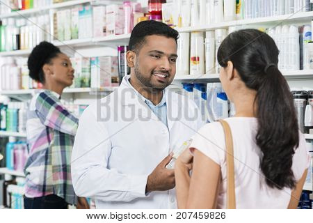 Young Chemist Assisting Female Customer