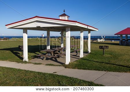 Coastal Michigan Beach Front Park. Waterfront park and picnic pavilion in the beach town of Manistee, Michigan with a lighthouse and Lake Michigan at the horizon.