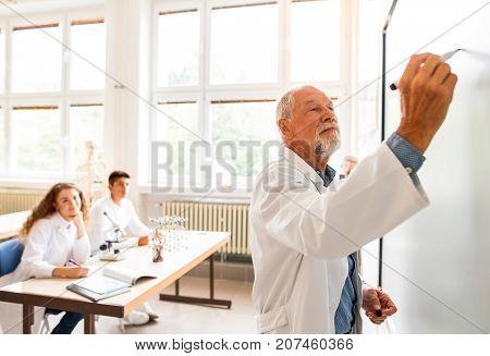 Senior teacher teaching biology to his high school students in laboratory.