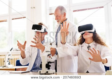 Senior teacher teaching biology to his high school students with virtual reality glasses in laboratory.