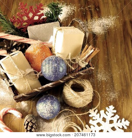 Basket full of Christmas attributes and present boxes on a wooden background. Christmas composition. Old photo filter