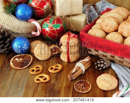 Biscuits with cinnamon surrounded by present boxes and Christmas attributes on a wooden background