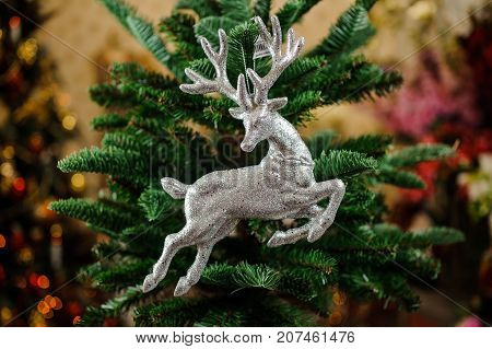 Christmas tree toy in the form of silver deer on the green background of fir tree