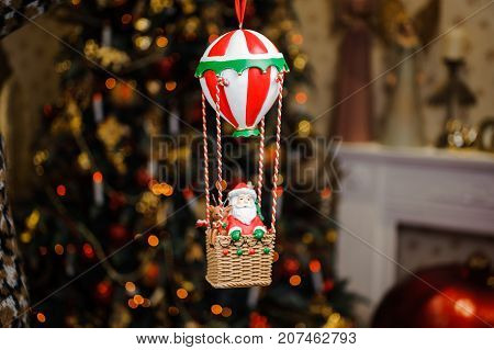 Cute Christmas tree decoration toy in form of Santa Claus in a balloon in the cozy and homely background of sparkling Christmas tree