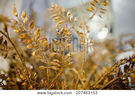 Beautiful Christmas decoration made of golden dried twigs with colorful iridescent rhinestones on the bright background
