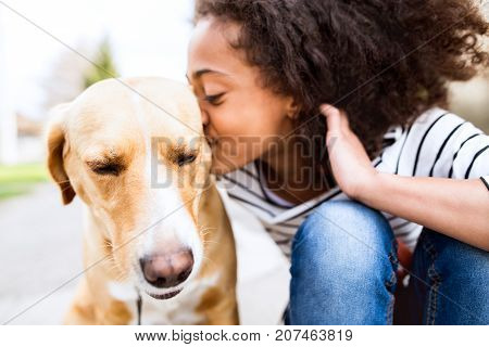 Beautiful african american girl with curly hair outdoors with her cute dog, kissing him.