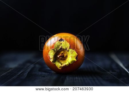 Chocolate persimmon crown on a wooden table and black background.