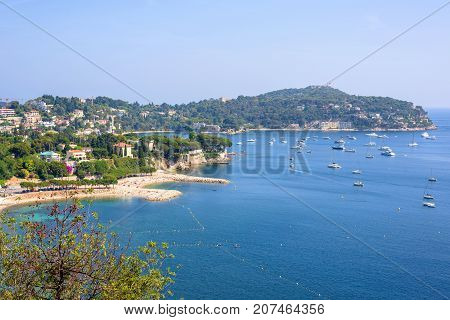 Beautiful daylight view from top of mountains to luxury resort villefranche sur mer and bay on french riviera at mediterranean sea Cote d'Azur in France, beach with boats cruising on water.