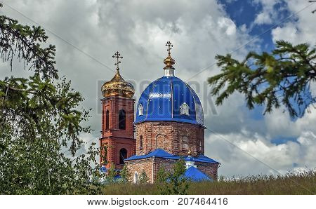 the old Church of red brick with blue and gold domes and crosses on the domes on the background the sky with clouds