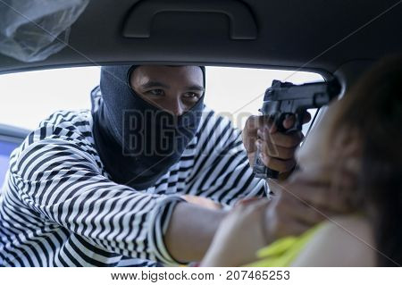 Thief pointing gun to woman's head try to robbery a car and ask for property of value such as moneycredit card pin code etc. Theft squeezing her neck she feeling shocked and scared. Thief concept