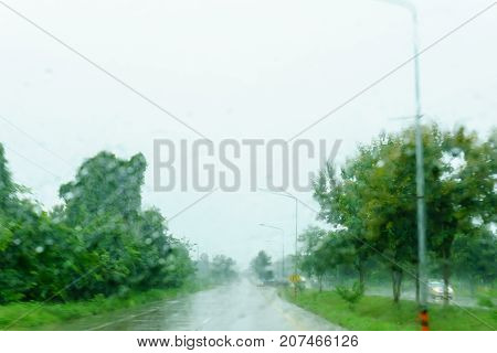 Blurred Beautiful Drop Of Rain On Glass Or Windows Surface With Road Background. Blurred Dew Or Rain