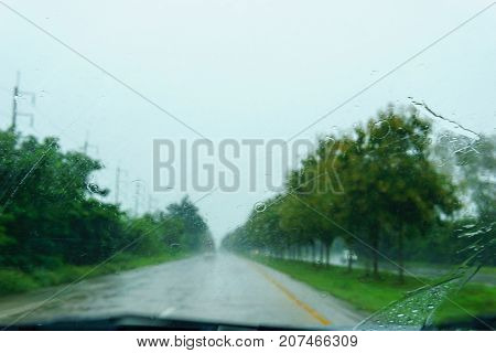 blurred beautiful drop of rain on glass or windows surface with road background. blurred dew or raindrop on glass surface for abstract backgroun