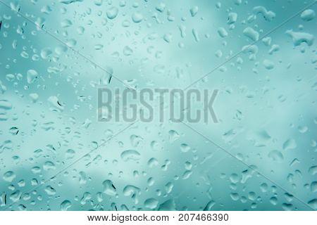 Blurred Beautiful Drop Of Rain On Glass Or Windows Surface. Blurred Dew Or Raindrop On Glass Surface