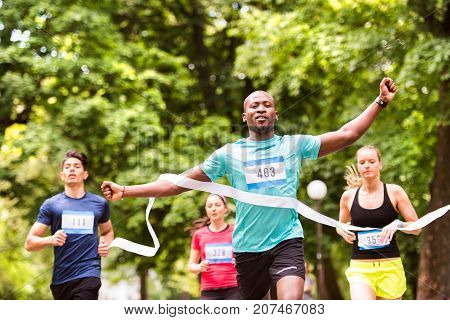 African man running in the crowd crossing the finish line.