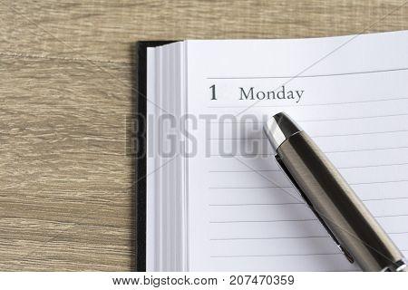 Μetal pen on a calendar with the page showing the first day of the month/week in a setting goals concept