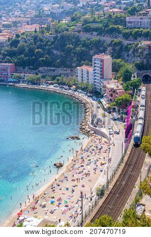 Beautiful daylight view from top of mountains to luxury resort villefranche sur mer and bay on french riviera at mediterranean sea Cote d'Azur in France. Tunnel train and railways.